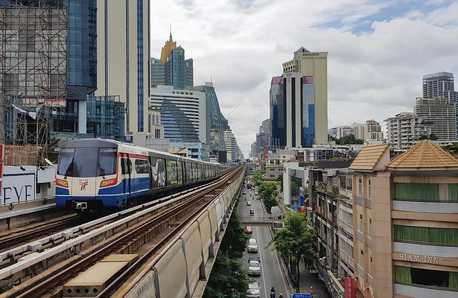 Sky train above the roads between the tall buildings in the centre of Bangkok