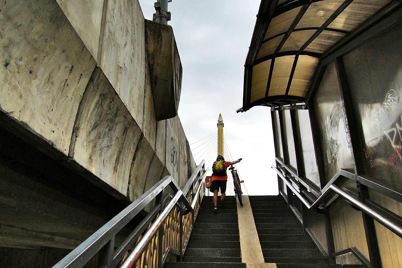 Man gaat met fiets de trap op van de brug
