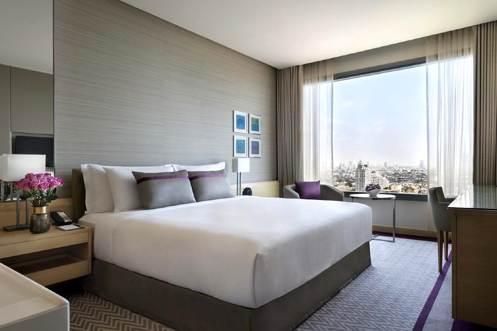 Avani+ Riverside Bangkok Hotel - Luxury hotel room with large bed and river view