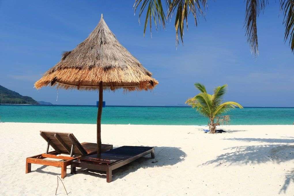 island with blue sky, white sand, palm trees and sunbeds