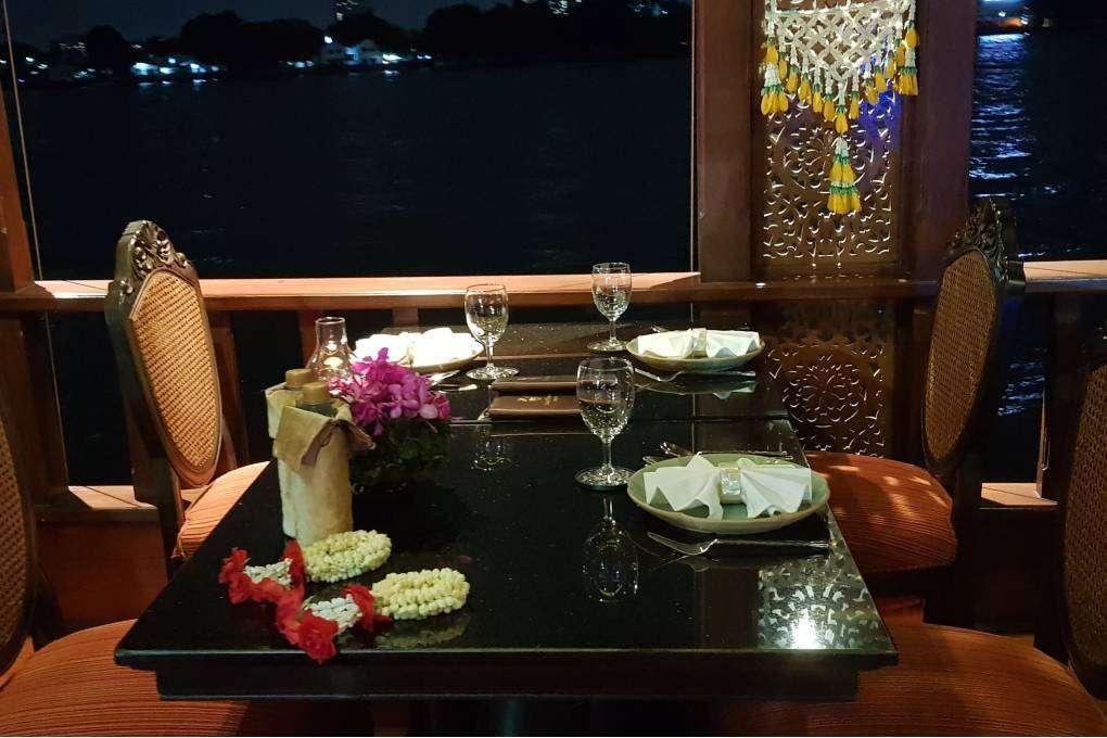Tafel met uitzicht op de Chao Phraya River tijdens de Baan Khanitha Cruise in Bangkok