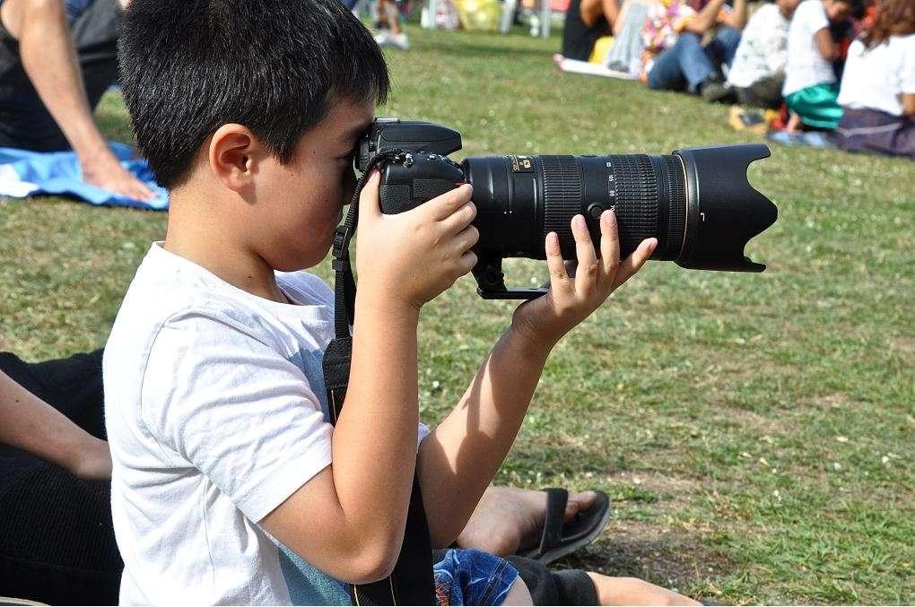 Thaise jongen met het fototoestel van paps