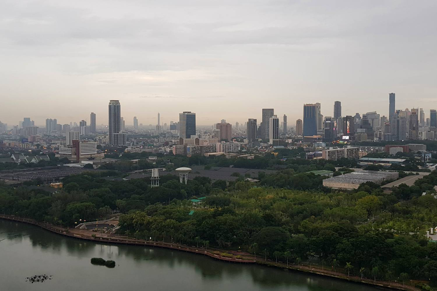 View from Long Table over the skyline of Bangkok with Lake Ratchada in Benjakiti Park in the foreground