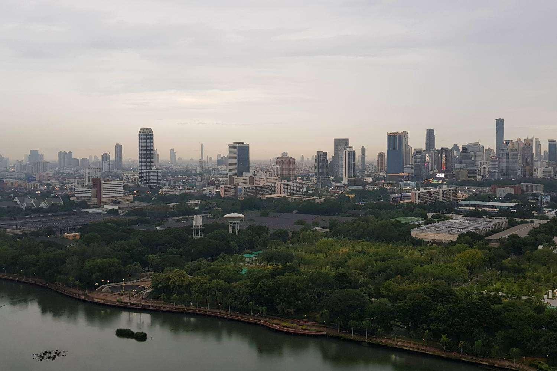 Uitzicht vanaf Long Table over de skyline van Bangkok met Lake Ratchada in Benjakiti Park op de voorgrond