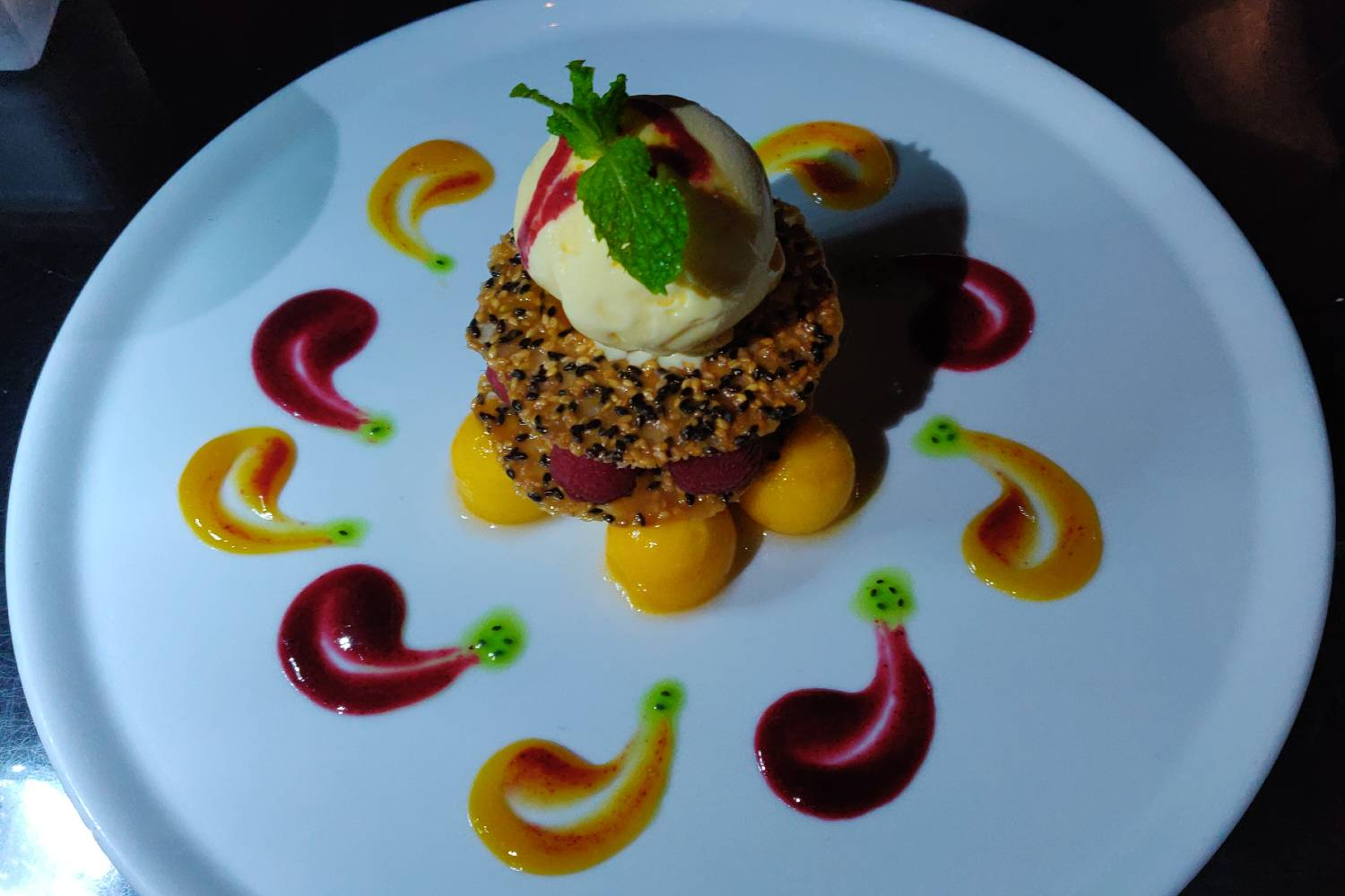 Raspberries and sesame crisp with passion fruit syrup and vanilla ice cream