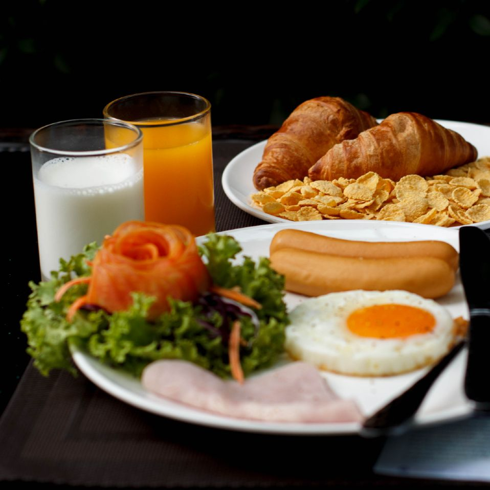 Breakfast with fried egg, sausages, croissants and juice at Hope Land Hotel Sukhumvit 8 in Bangkok, Thailand.