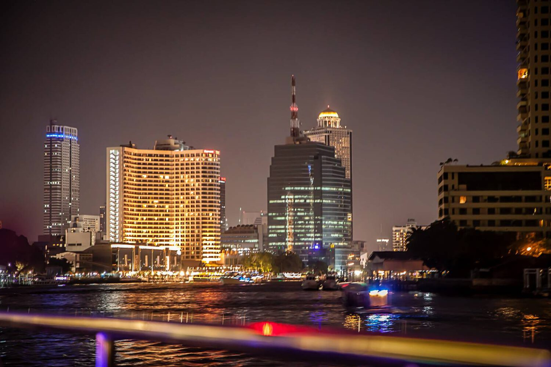 uitzicht op verlichte torenflats aan de rivier vanaf de boot.