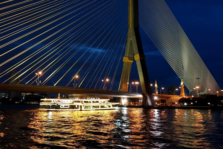 Sprookjesachtig verlichte Rama VIII brug met een cruiseboot die er onderdoor vaart.