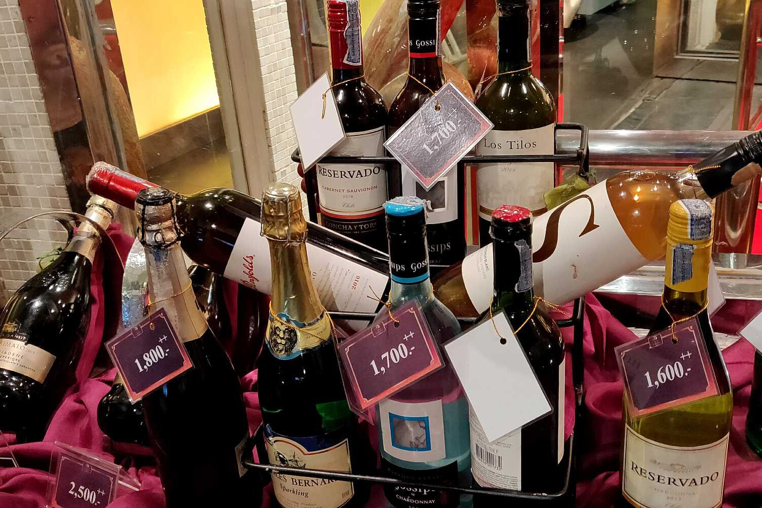 bottles of wine, champagne and beer on a table with price tags