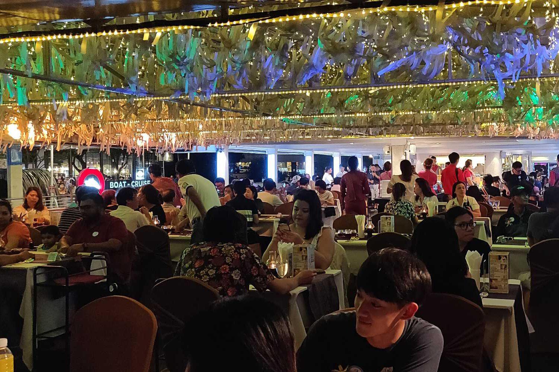 Tafels met etende mensen aan boord van de cruise