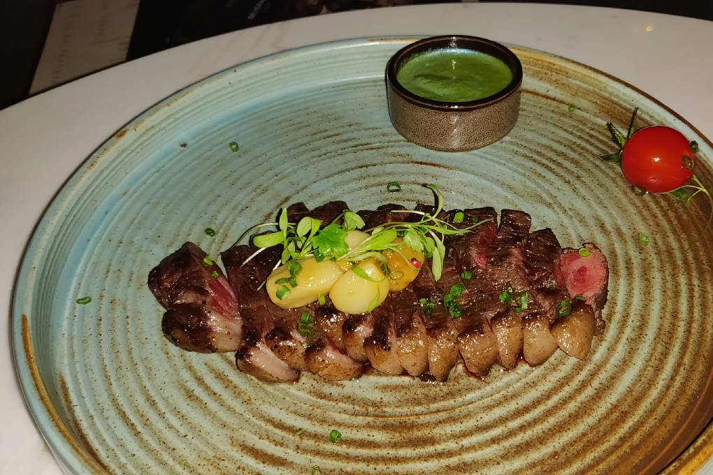 Wagyu steak and potatoes on plate with sauce dish