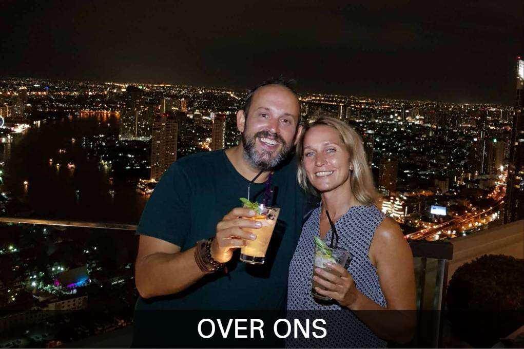 Riel En Ilonka Op Een Sky Bar Met Allebei Een Cocktail In Hun Handen Met Op De Achtergrond Bangkok