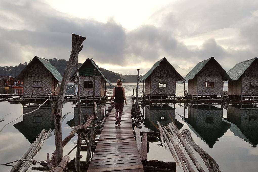 Ilonka op houten loopplank op een meer met kleine drijvende hutjes