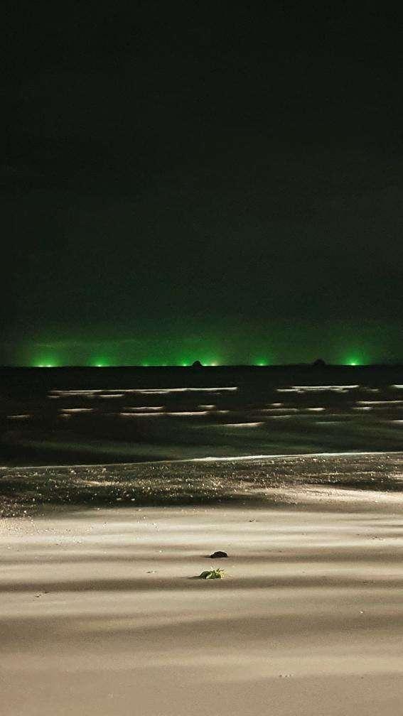 Inktvisvissers in de zee van Ao Nang tijdens de nacht net de typerende groene lichten op zee