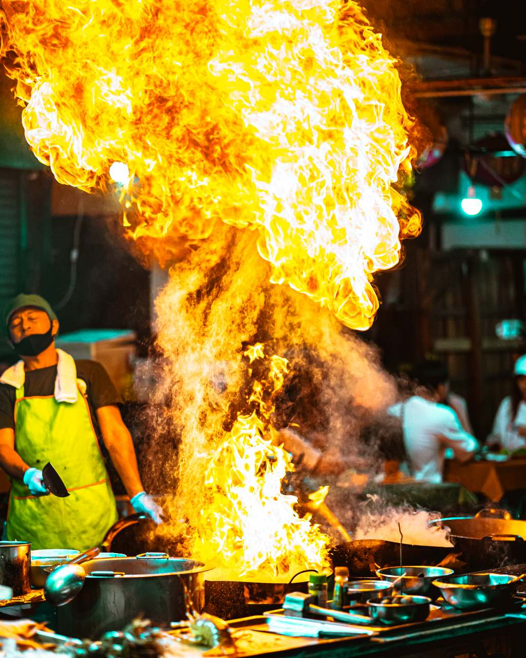 Flame while a man is preparing street food in Bangkok