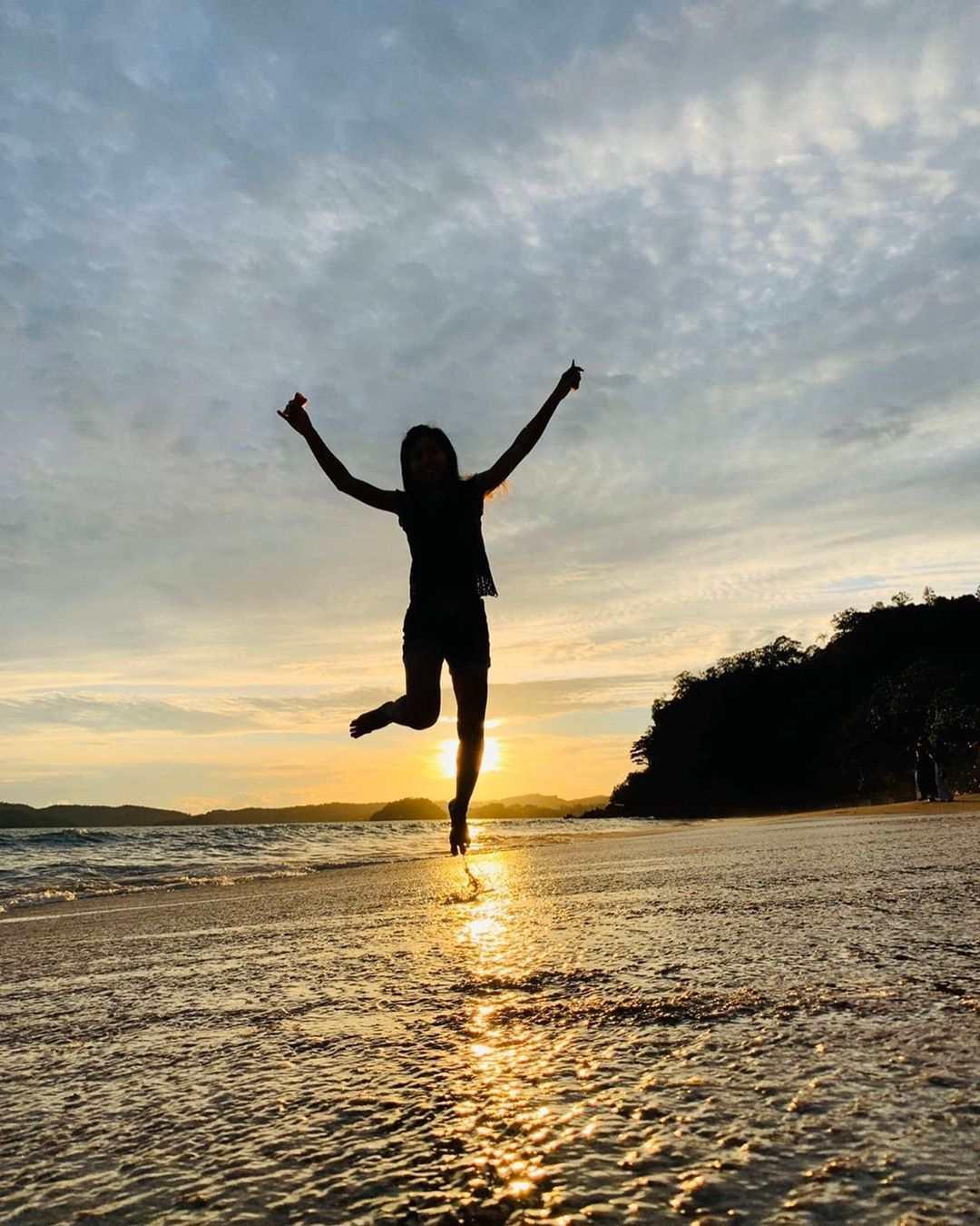 Meisje springt omhoog tijdens de zonsondergang op het strand van Ao Nang