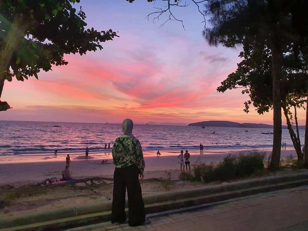 Iemand bekijkt de zonsondergang vanaf de boulevard van Ao Nang