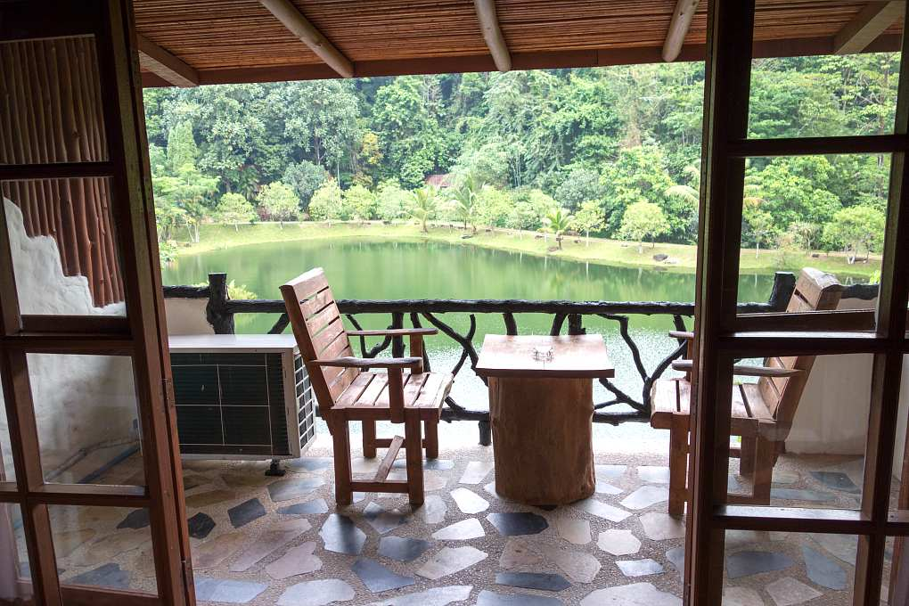 Balcony with wooden chairs and table overlooking lake surrounded by jungle