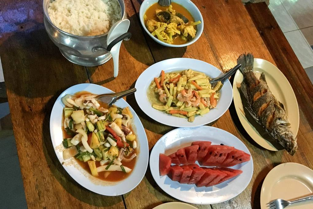 Set menu of Thai dishes with fish, corn , rice and melon
