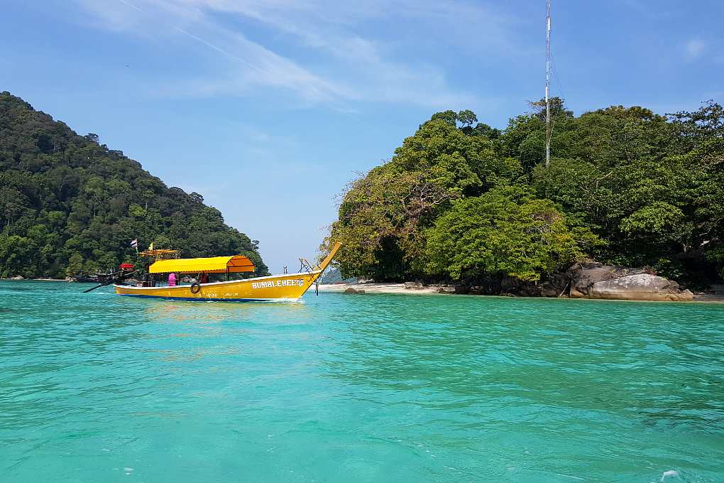 A yellow longtail boat sails in the blue water around the Surin Islands.