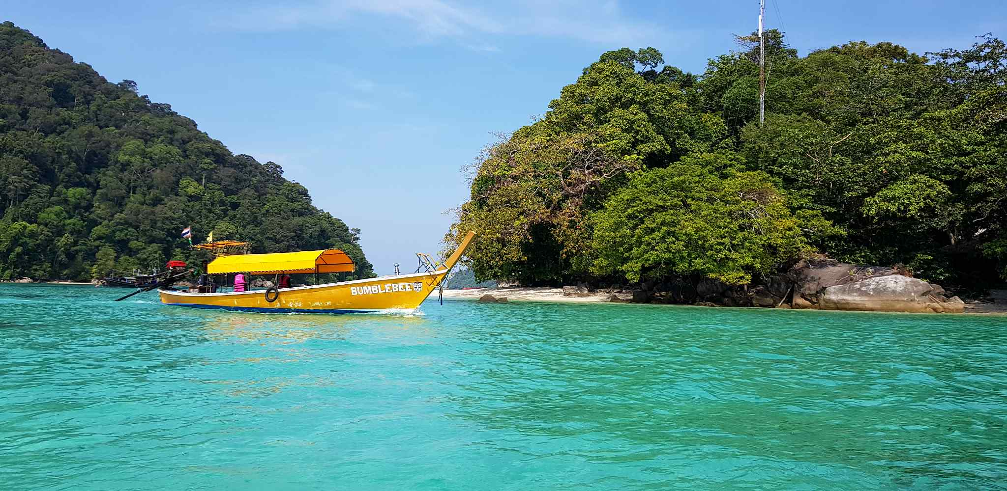 yellow longtail boat in the blue waters of Mu Ko Surin National Park