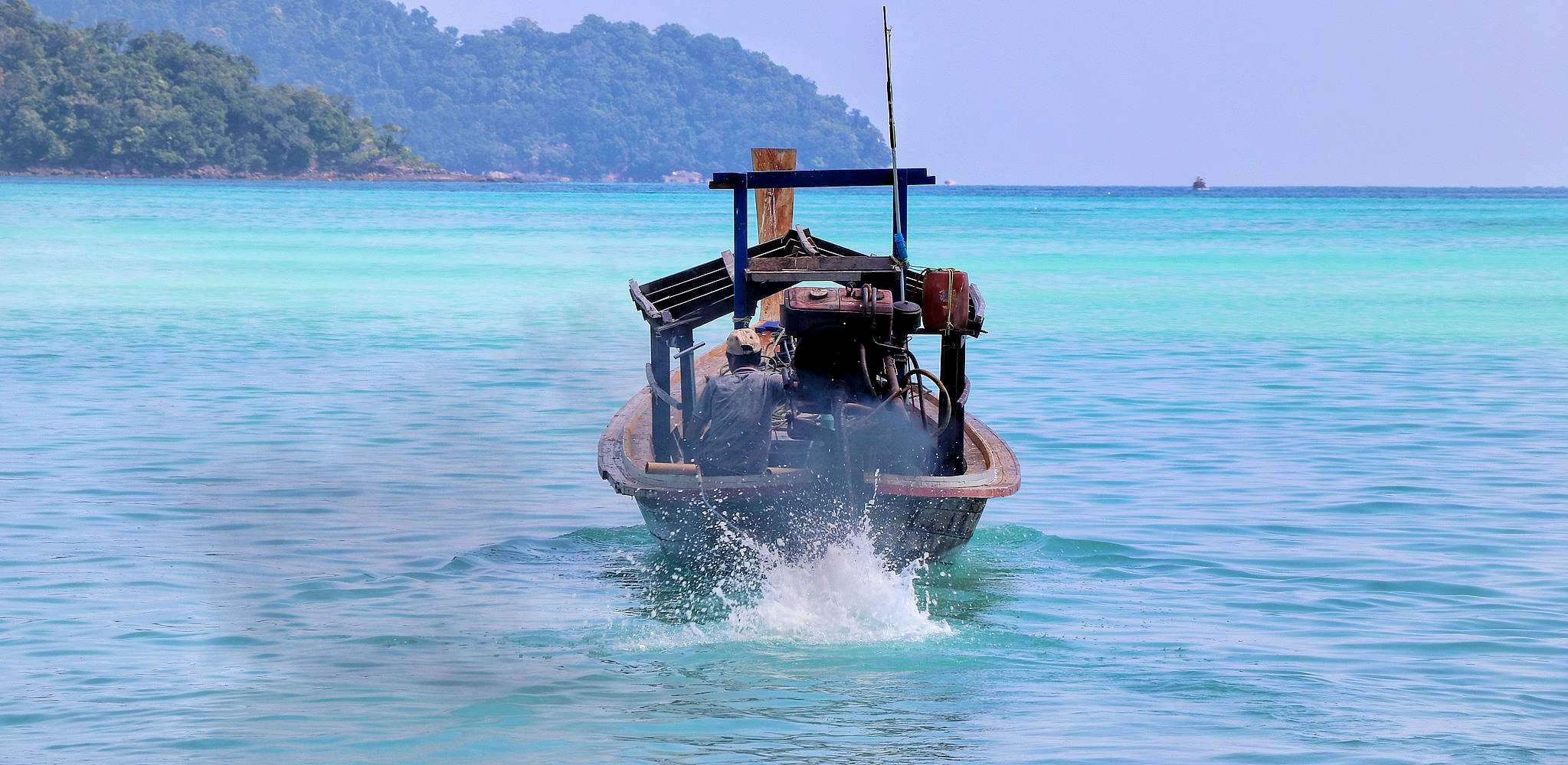 longtail boat in the water with smoking engine