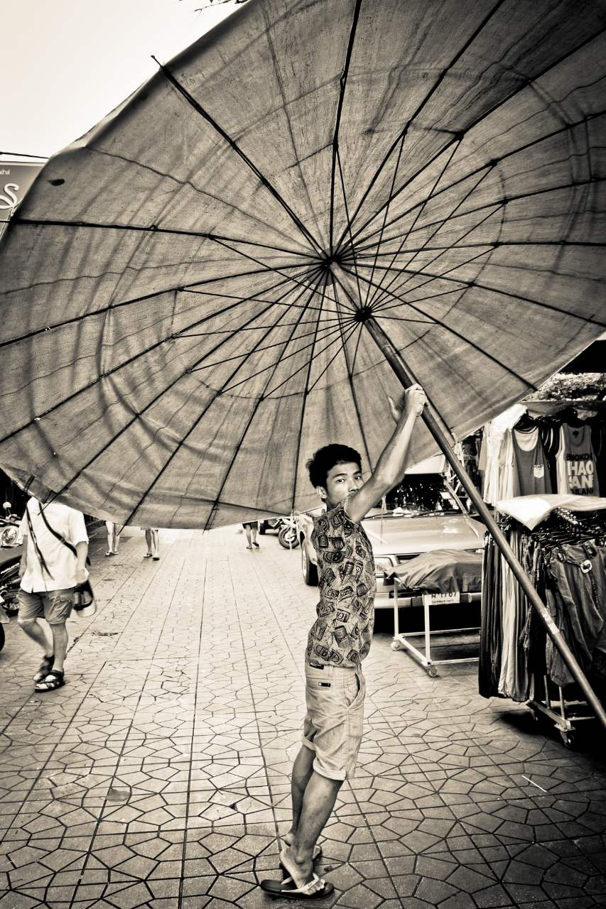 Taken in the early morning on the street of Rambutri, Bangkok, a street vender sets up a large umbrella to shield him from the sun in the day's building heat.