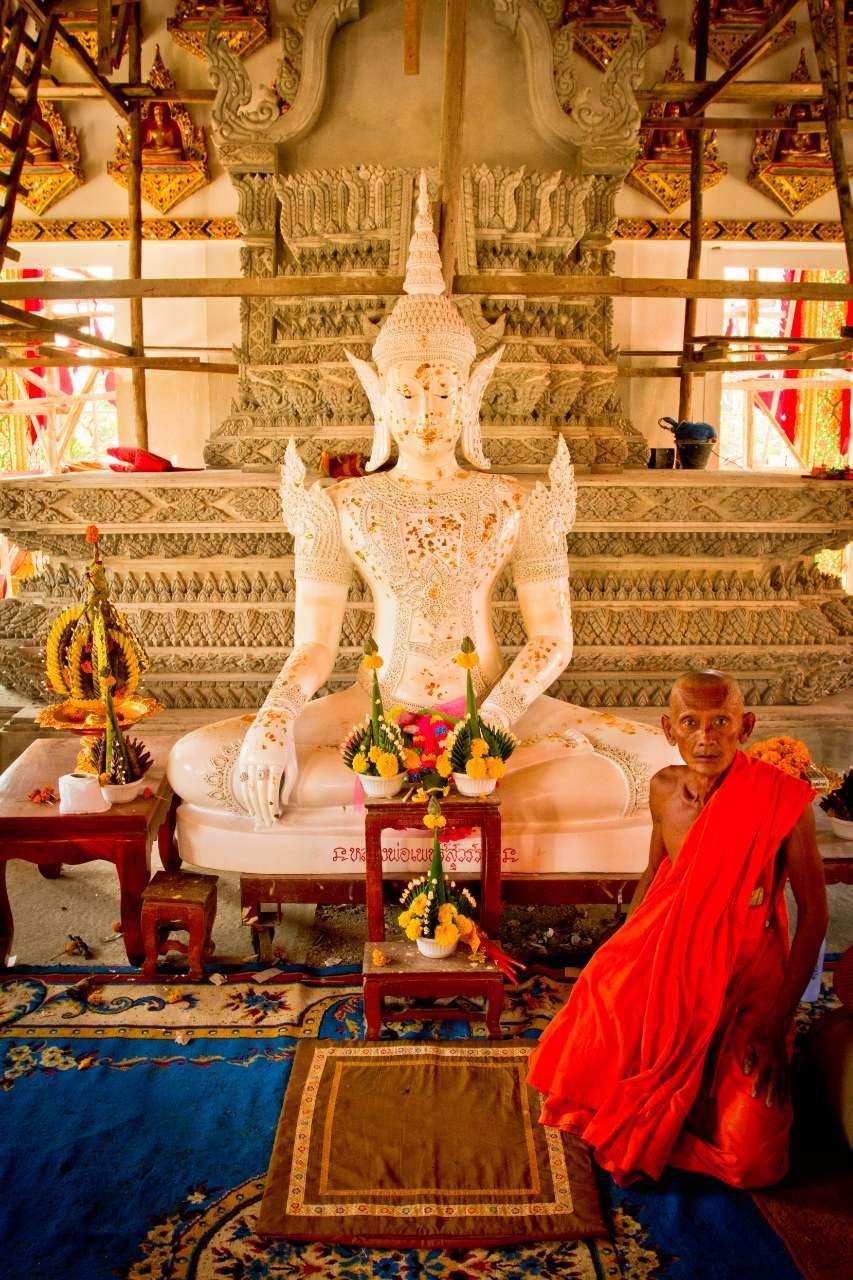 Een oudere monnik zit naast een Boeddhabeeld in een nieuwe tempel van Sukhothai.