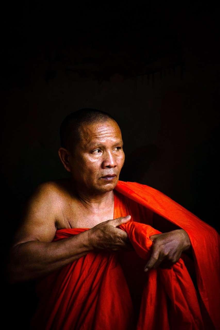 Onder Koh Samui's Big Buddha Temple (Wat Phra Yai) bereidt een monnik zich voor op een avondje meditatie.