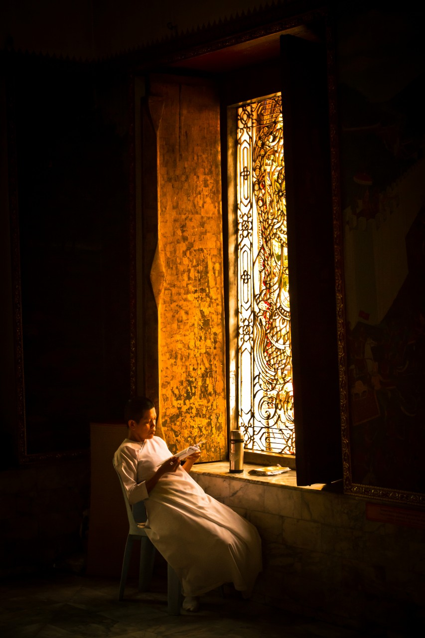 A Buddhist nun sits reading in rich Bangkok dusk sunlight in the temple of Wat Chana Songkhram.