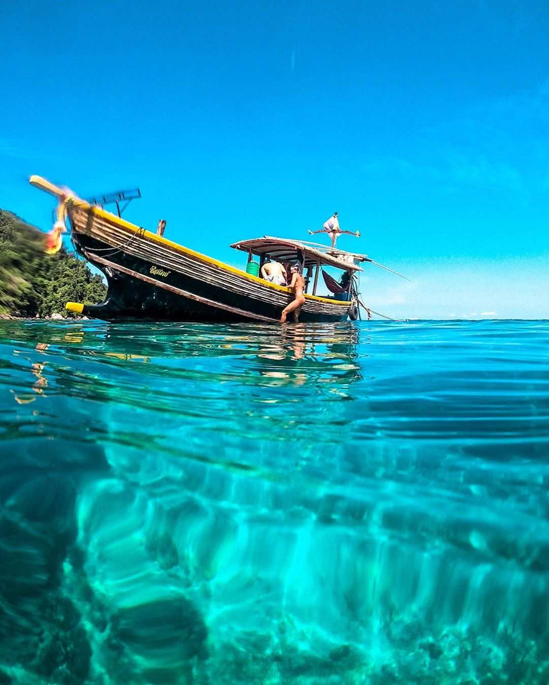 A longtail boat in the blue-green seawater of the Surin Islands