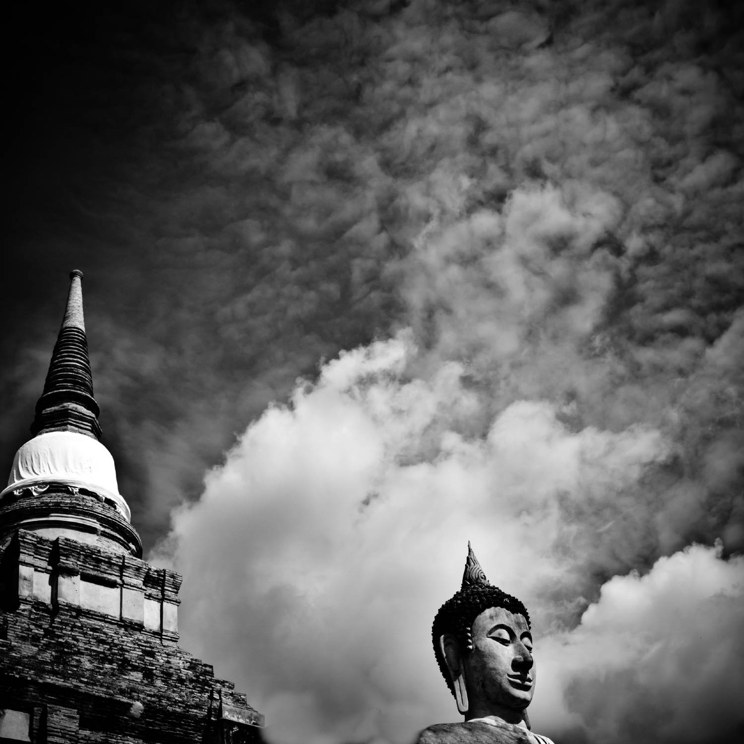 A Buddha statue and stupa of Ayutthaya under a backdrop of clouds.