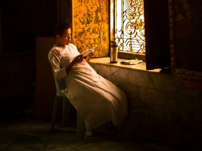 A Buddhist Monk Reading At A Large Window
