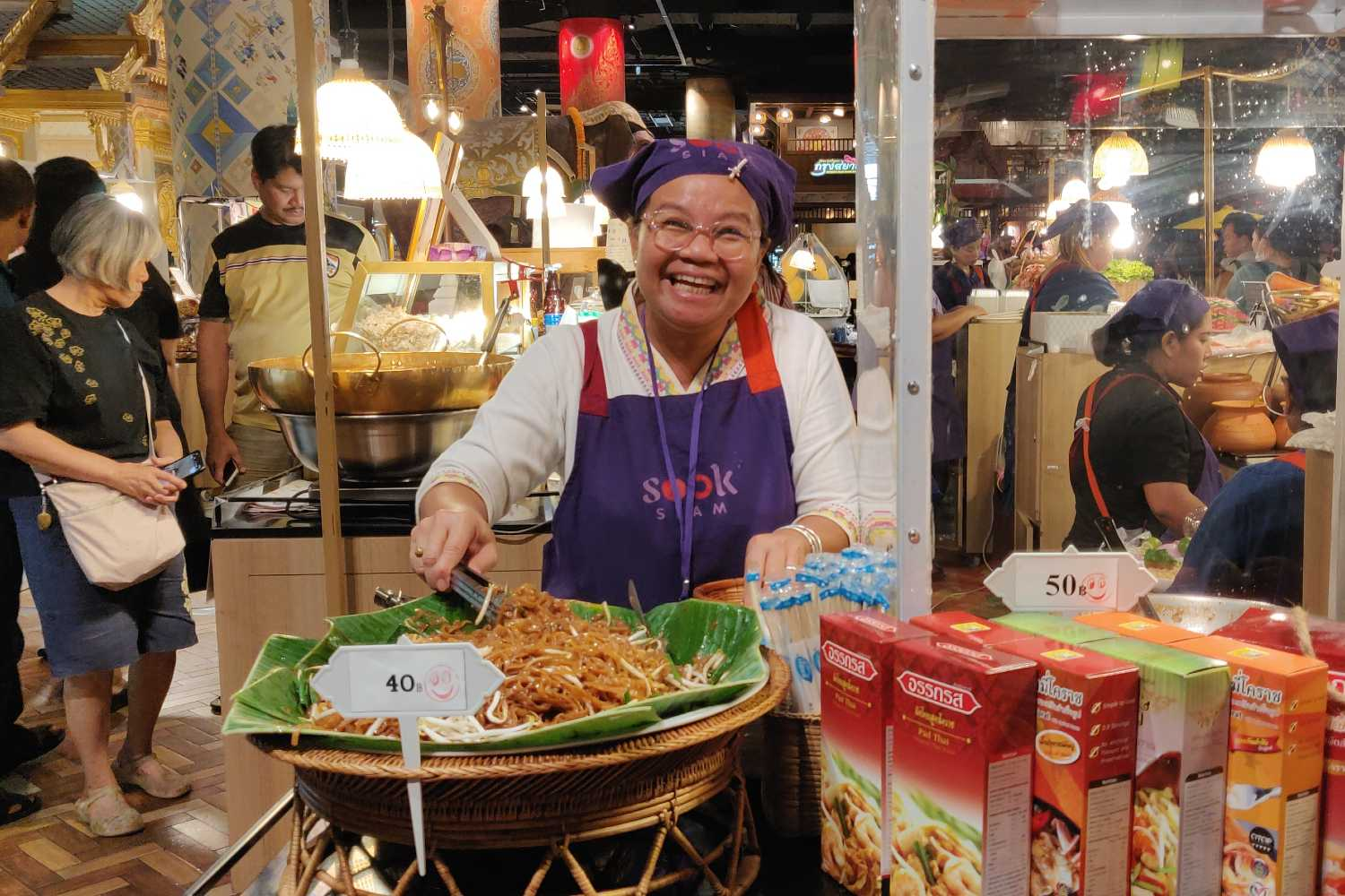 Cheerful lady prepares padthai in SookSiam in ICONSIAM