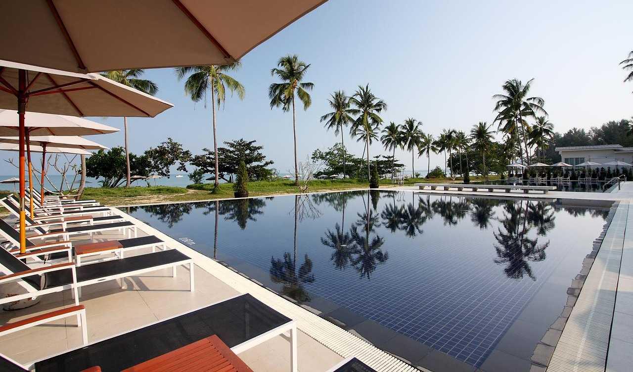 Sunbeds with parasols at the pool at Kantary Beach Hotel Villas & Suites Khao Lak
