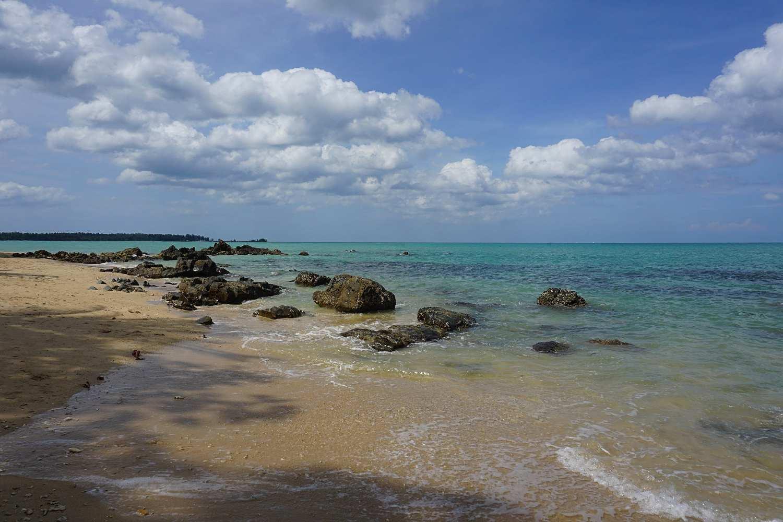Rotsen in de heldere blauwe zee en strand van Khao Lak