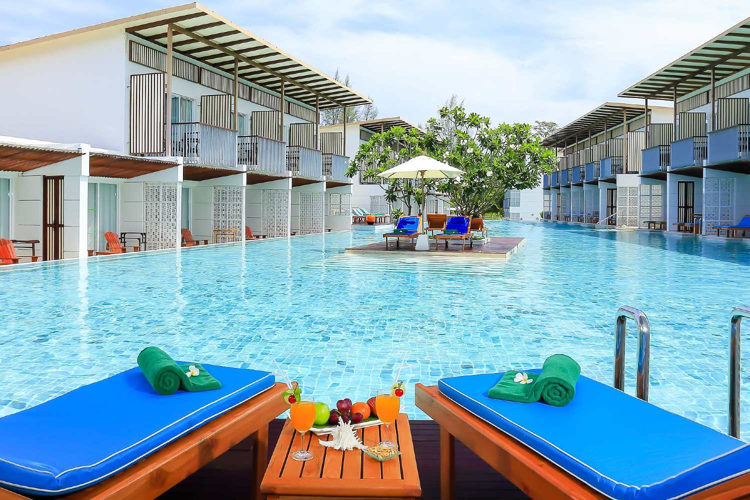 Sun loungers on the private terrace of the hotel room with access to the large swimming pool of the Briza Beach Resort