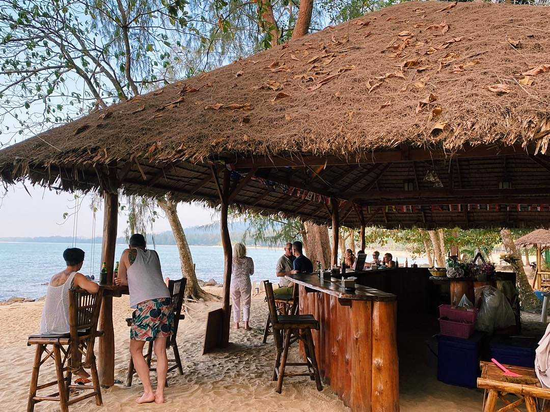 People at bar with thatched roof on the beach