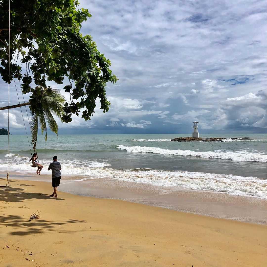 Schommel op het strand van Nang Thong Beach met op de achtergrond de vuurtoren in zee