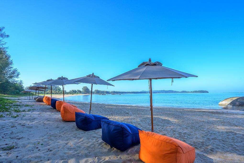 Kleurrijke zitzakken en parasols op het Poseidon Beach / Lam Kaen Beach