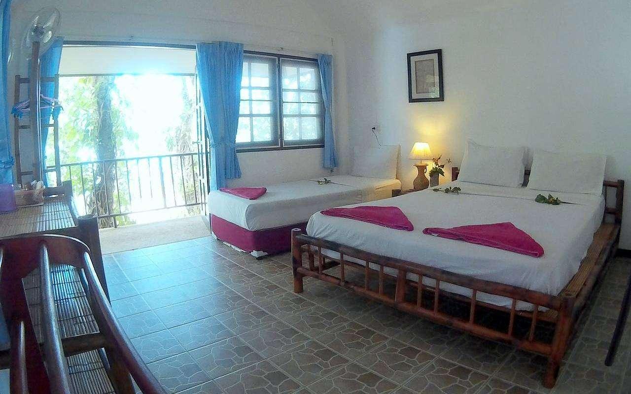 eenvoudige bungalowkamer met een tweepersoonsbed en een los bed