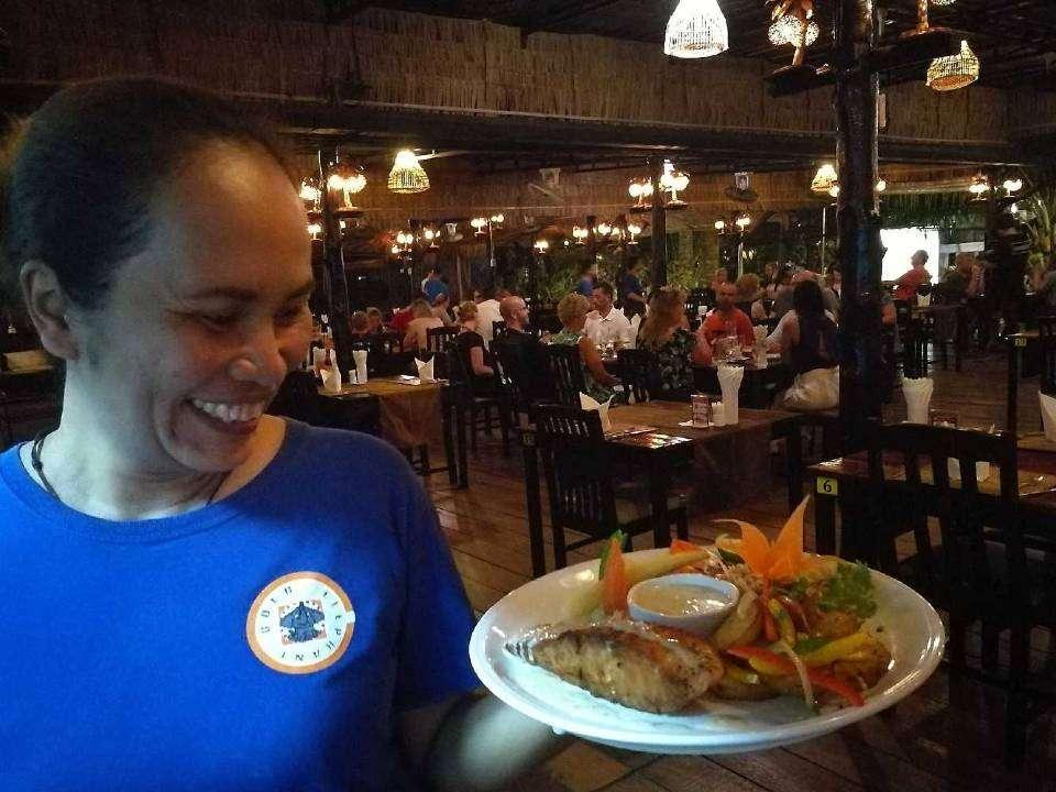 Serveester met visgerecht met op de achtergrond het Gold Elephant Restaurant