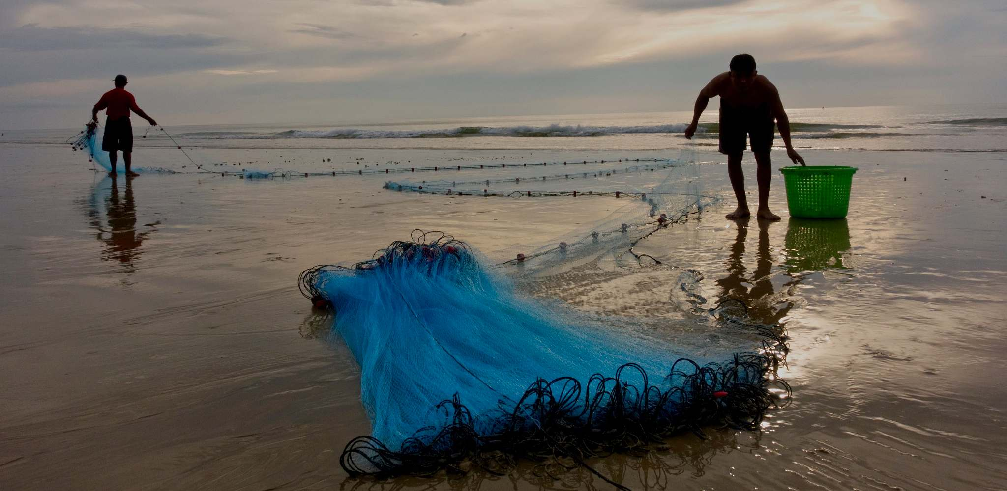 Fishermen with fishing nets on the beach of Bang Sak