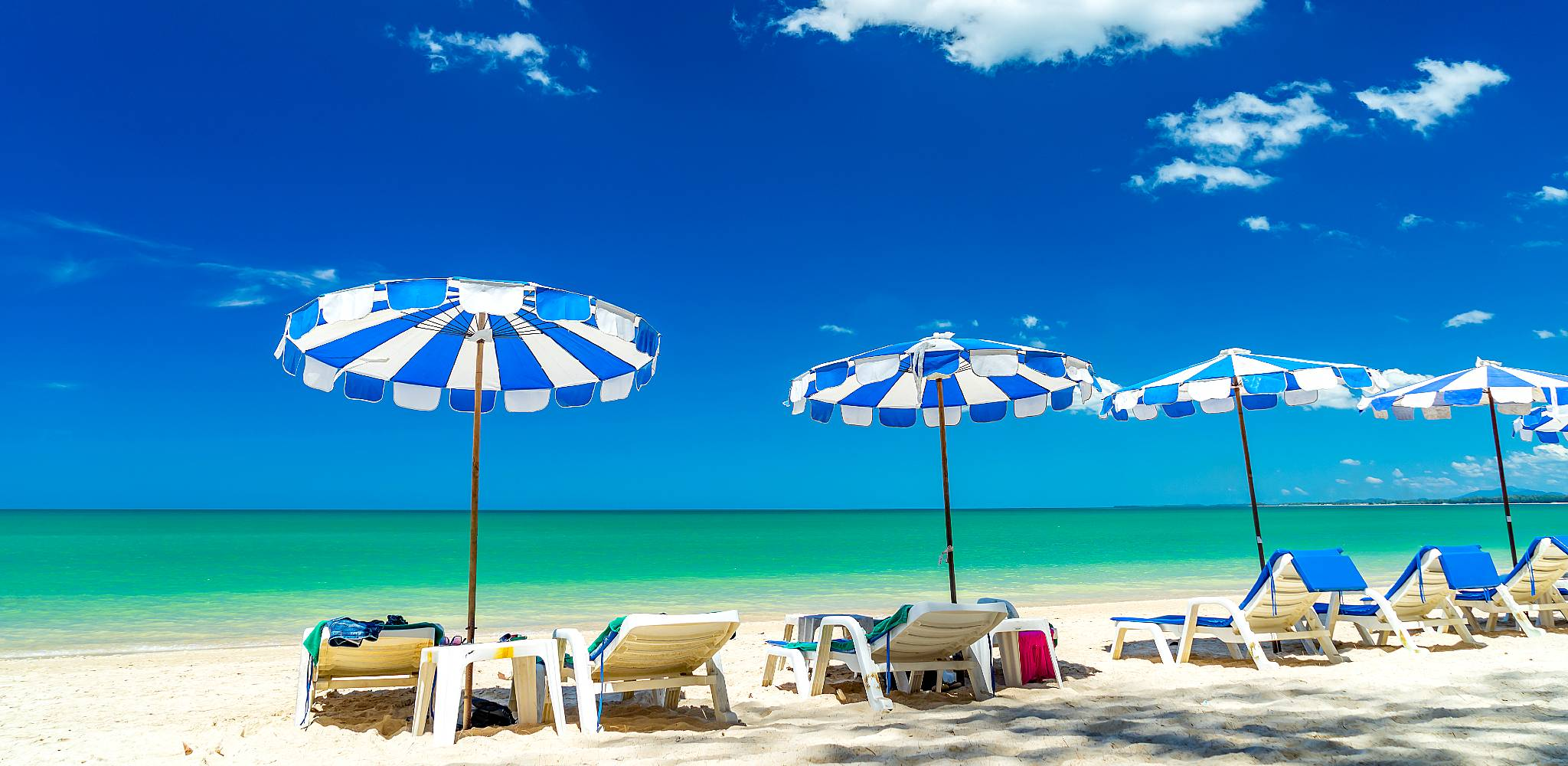 white beach with sunbeds and umbrellas on a blue sea