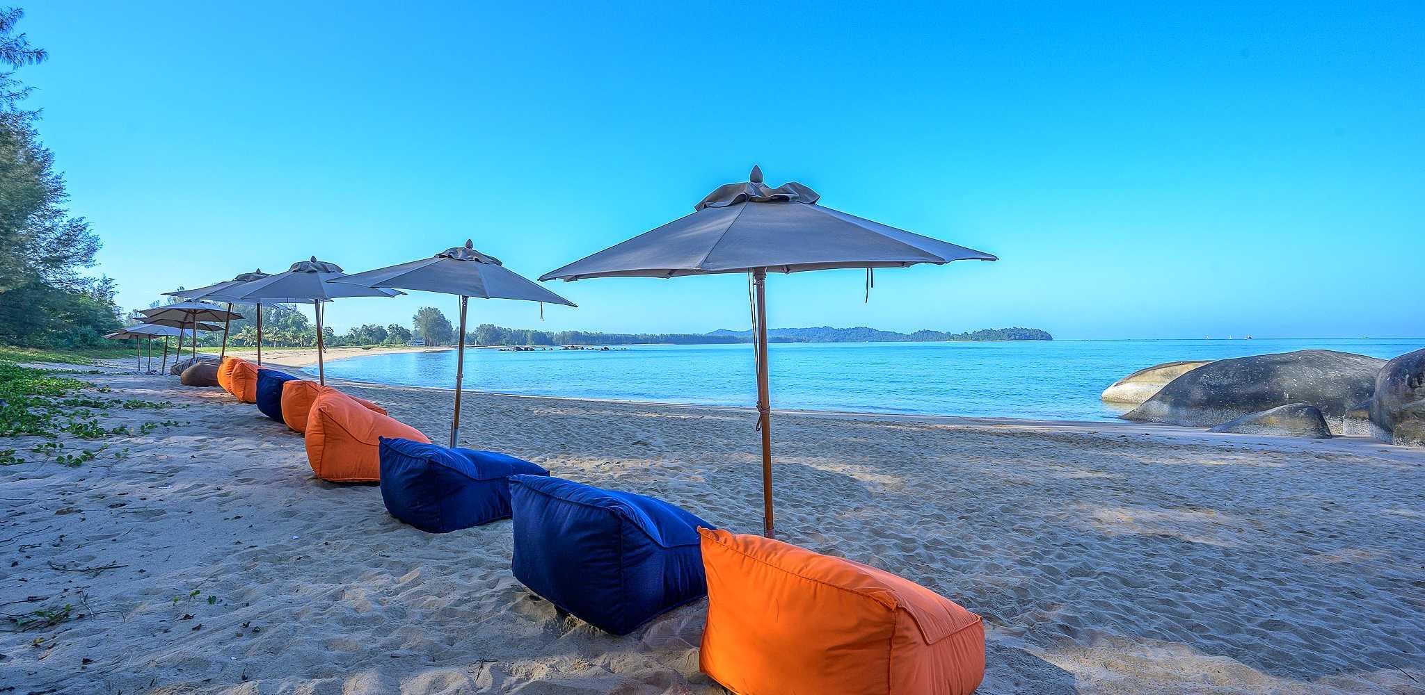 Kleurrijke zitzakken en parasols op het Poseidon Beach Strand