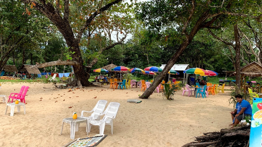 Colourful parasols, plastic tables and chairs under the shade of the trees