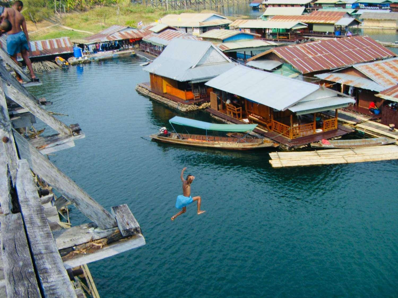 Sprong in het water vanaf de Mon Bridge in Sangkhla Buri, Thailand