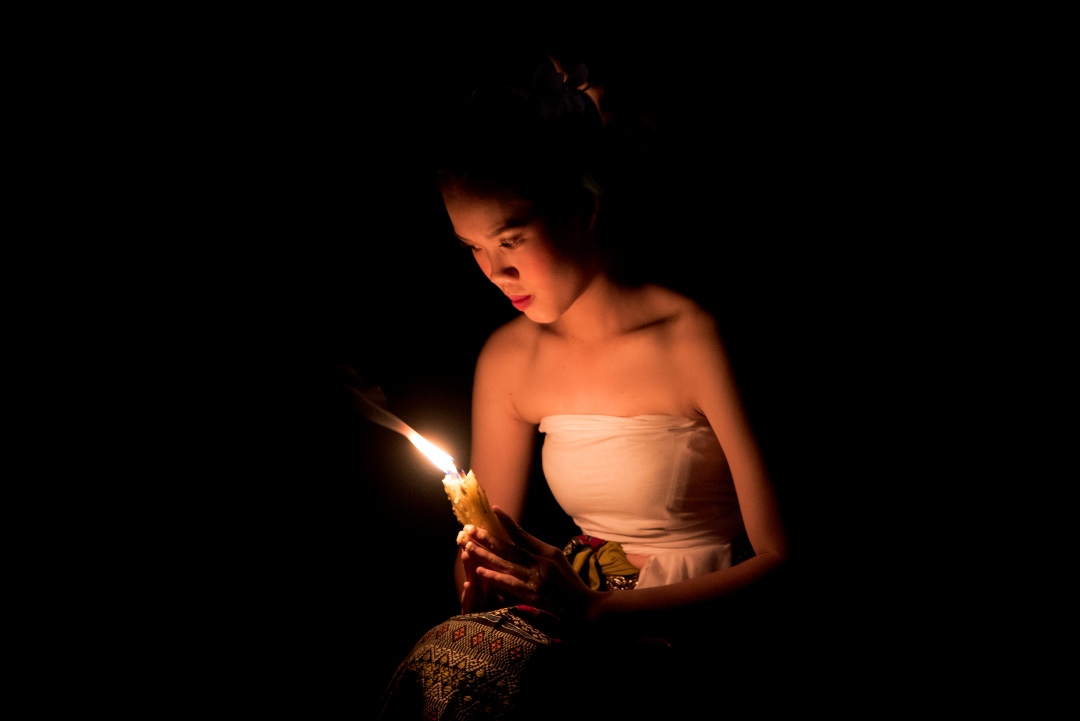 Girl with burning candle during Loy Krathong 2020