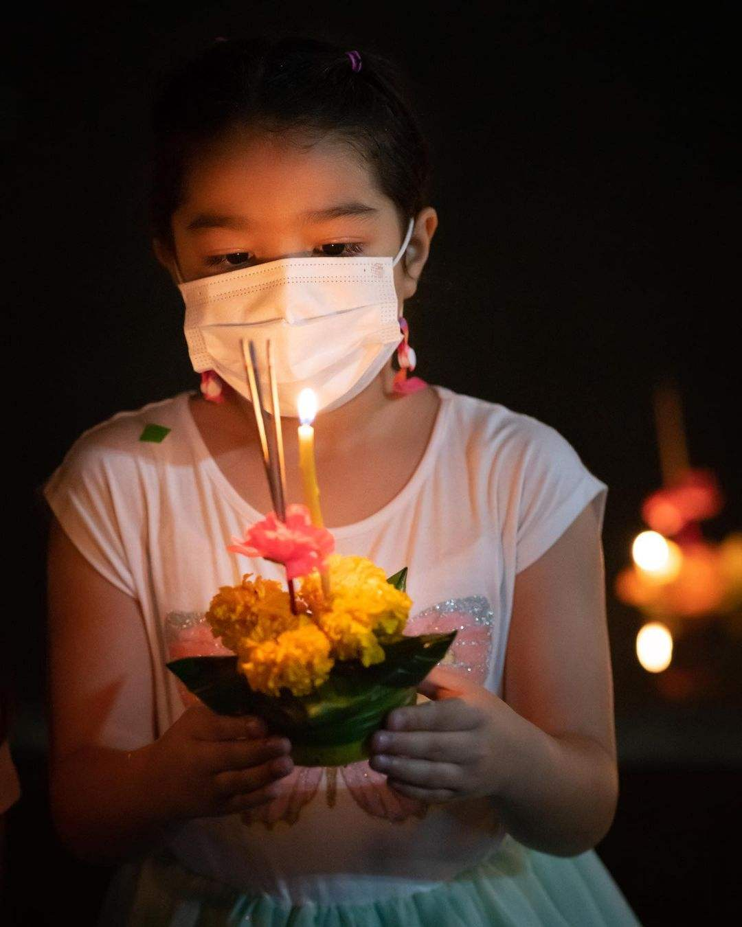 Girl with mouth msask on and a Krathong in her hands during Loy Krathong 2020