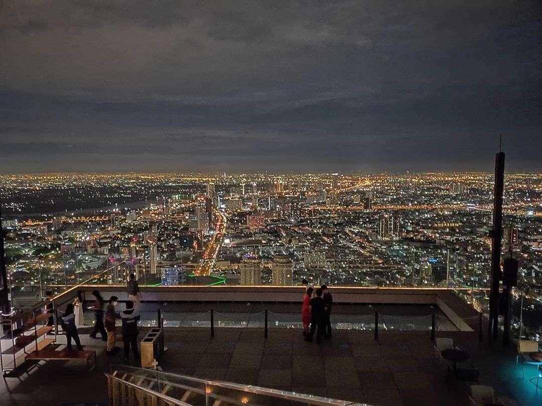 Zicht over de skyline van Bangkok tijdens de avond vanaf de King Power MahaNakhon